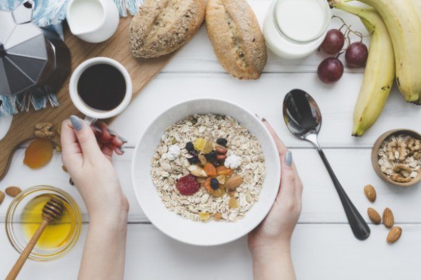 crop-hands-holding-coffee-and-muesli_23-2147758210
